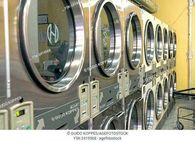 New York, USA. Double row of washing machines and dryers in one of the many local launderettes on 8th Avenue, Brooklyn
