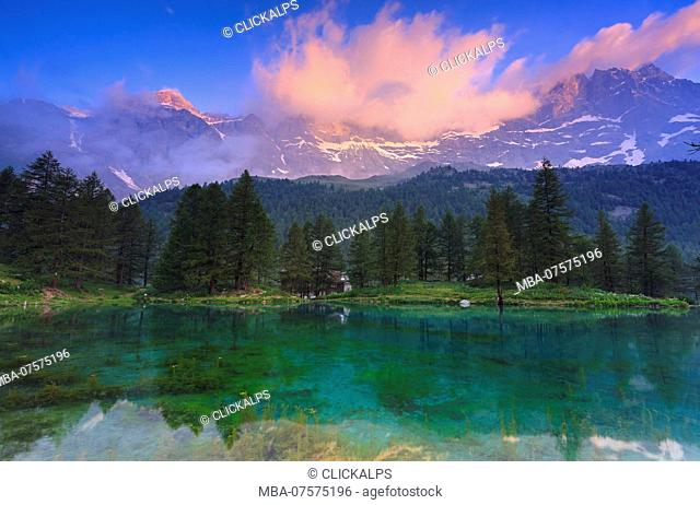 Cloud illuminated by the colors of dawn is reflected in Blue Lake, Blu Lake, Cervinia, Valtournanche, Aosta valley, Italy, Europe