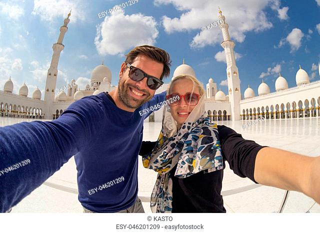 Tourist couple taking selfie in the courtyard of famous Sheikh Zayed Grand Mosque in Abu Dhabi, United Arab Emirates