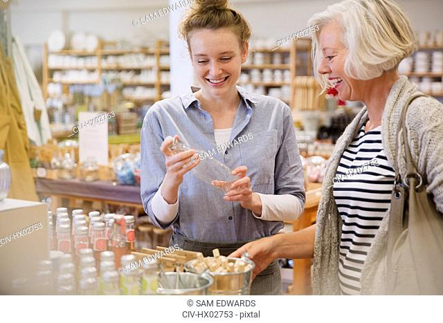 Mother and daughter shopping, browsing glass bottles in shop
