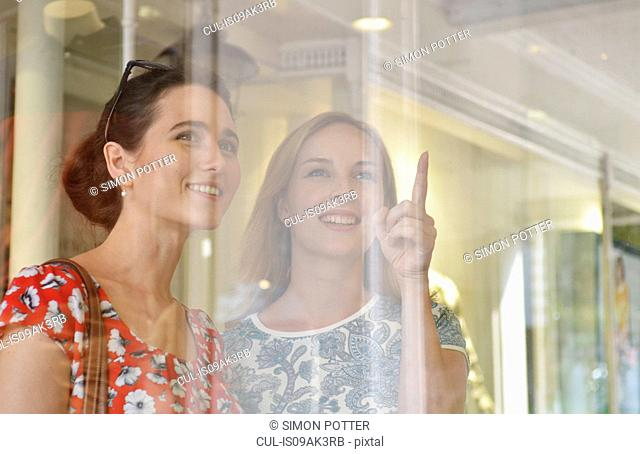 Two young women looking and pointing at shop window