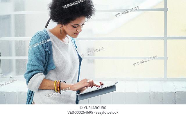 Pretty young woman using a digital touchpad, looking out the window and smiling