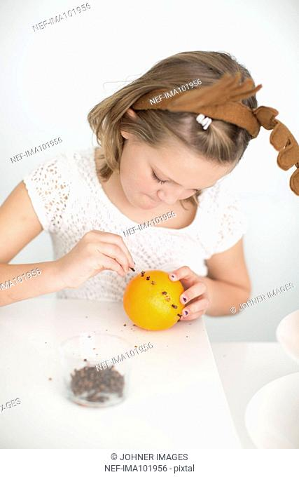 Girl preparing decoration with orange and cloves