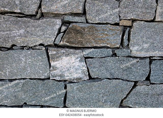 Close-up of granite rock blocks joined together without mortar forming a wall of alpine mountain refuge