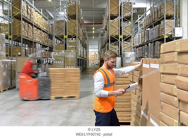 Man with clipboard in factory hall and moving forklift