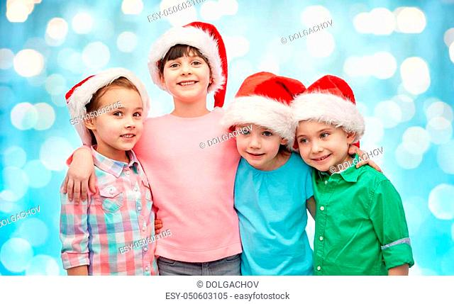 childhood, christmas, holidays, friendship and people concept - group of happy smiling little children in santa hats hugging over blue holidays lights...