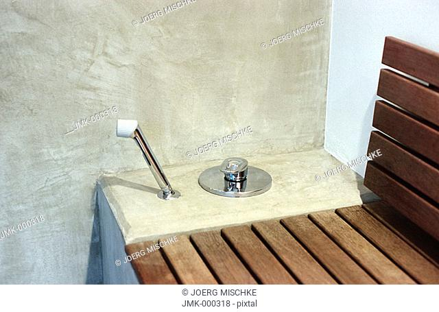 Shower, hand shower and a wooden bench in a spa
