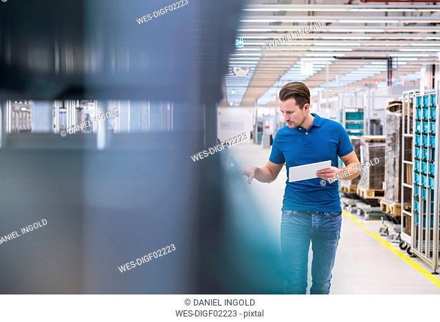 Man with tablet looking at tugger train in industrial hall