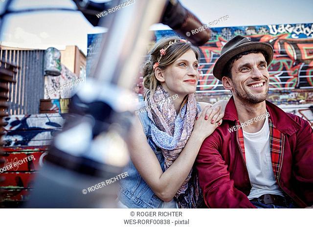 Germany, Hamburg, St. Pauli, Couple sitting in front of graffiti, smiling