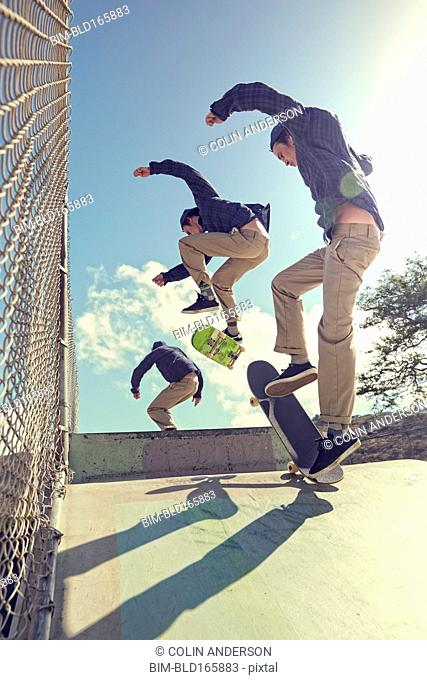 Multiple exposure of Caucasian man performing trick in skate park