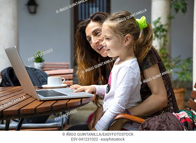 girl four years old sitting on mother legs, surfing internet and smiling watching laptop pc computer, with coffee cup on brown wooden table