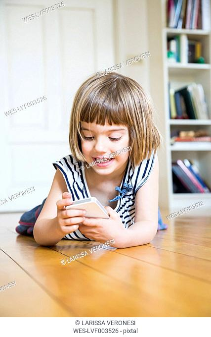 Portrait of smiling little girl lying on wooden floor with smartphone