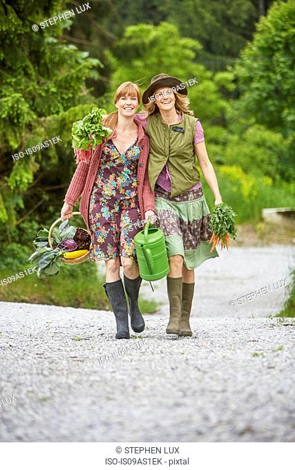 Two women carrying vegetables along rural road