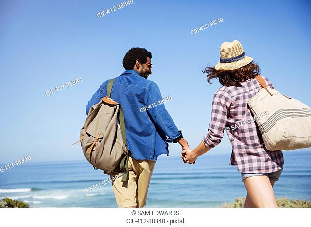 Affectionate multi-ethnic couple holding hands, walking on sunny summer ocean beach