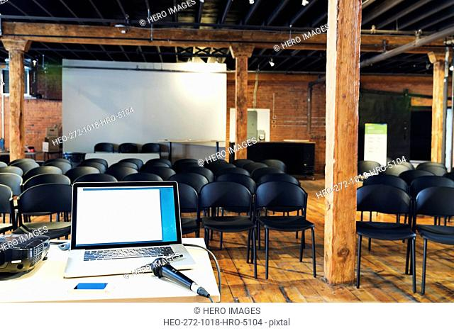 Interior of conference room with laptop and microphone on table
