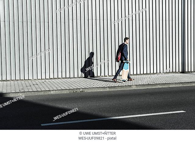 Young businessman walking with skateboard on pavement