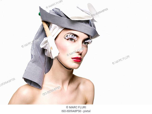 Mid adult woman wearing fashionable hat against white background
