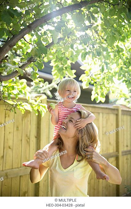 Playful mother carrying daughter on shoulders below apple tree in sunny backyard
