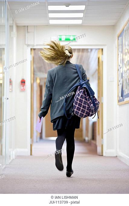 Middle school student running in school corridor