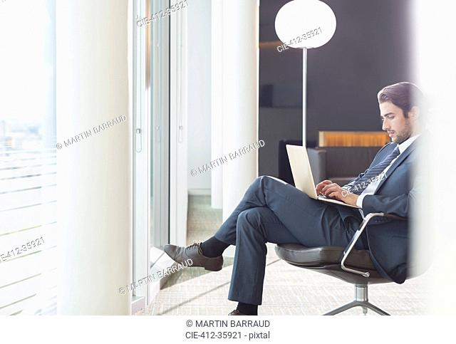 Businessman using laptop in office lounge