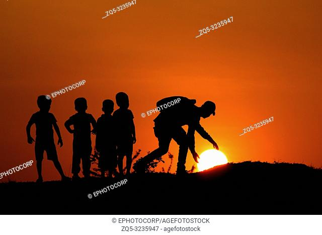 Silhouette of man with the kids touching Sun, Maharashtra, India