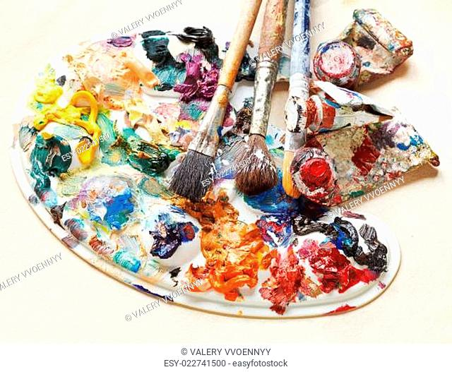 artistic pallette with oils, paint brushes, tubes