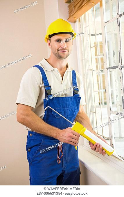 Man putting filling between window and wall