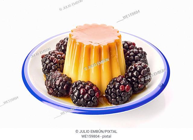 homemade egg flan with blackberries on plate