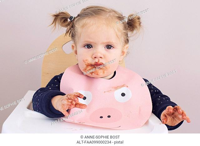 Baby girl sitting in high chair with food smeared on her face and hands