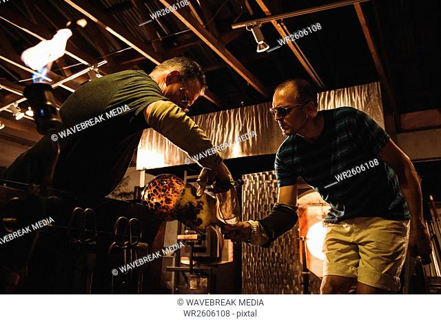 Team of glassblowers shaping a molten glass