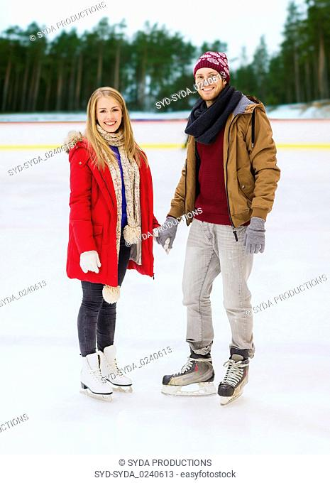 happy couple holding hands on skating rink