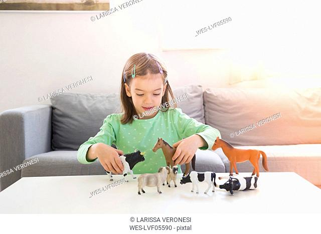 Little girl playing with animal figurines at home