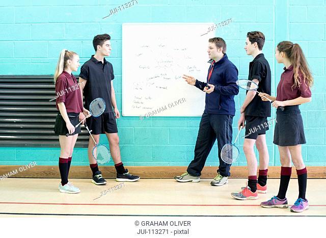 Gym teacher teaching high school students badminton in gym
