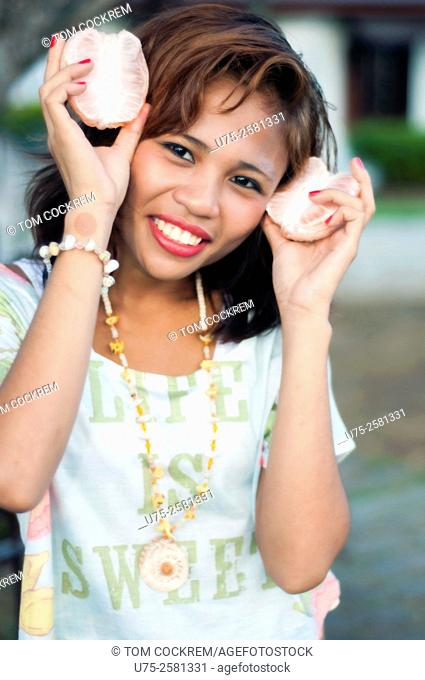 Attractive Asian woman with citrus fruit on location, Philippines