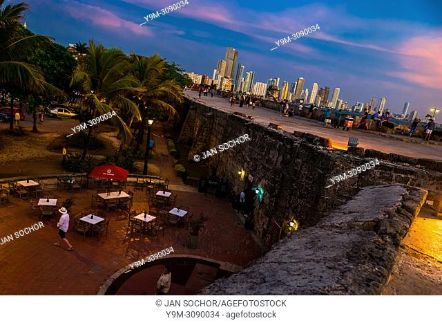 Tourists walk on and along the stone walls, surrounding the colonial walled city, at twilight in Cartagena, Colombia, 14 April 2018