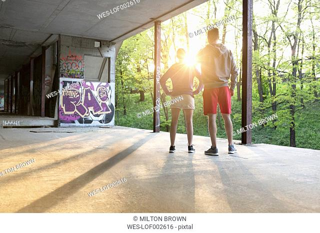 Young athletic man and woman standing at underpass