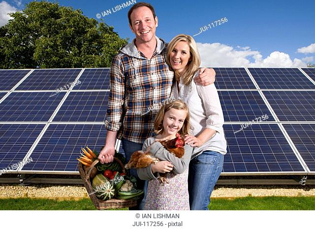 Family With Homegrown Food Standing By Solar Panels
