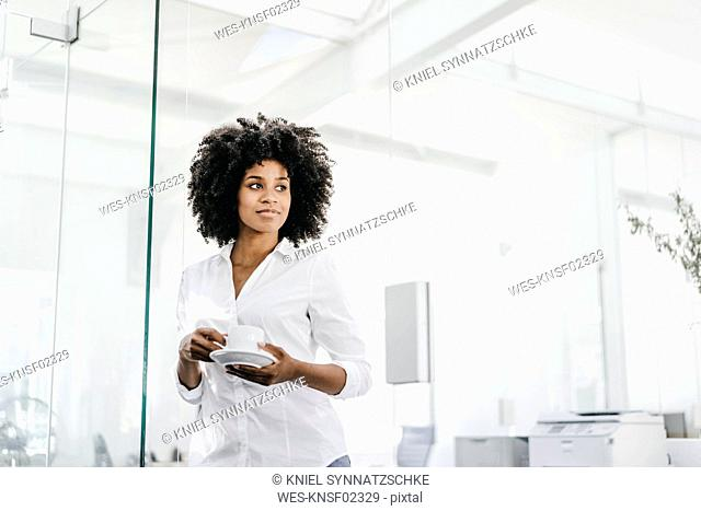 Portrait of young woman holding cup of coffee in office