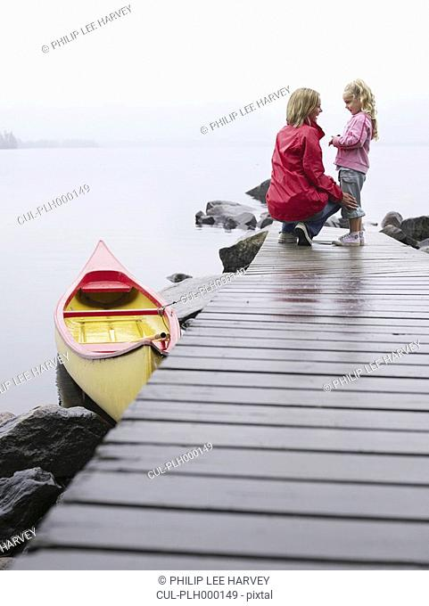 Woman with young girl standing on a dock smiling