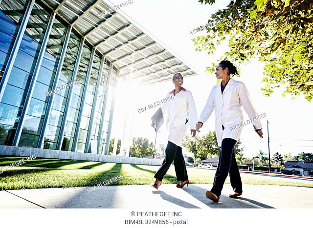 Doctors walking and talking outdoors at hospital