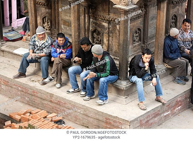 Men resting and drinking chai at Bhimeleshvara Temple in Durbar Square - Kathmandu, Bagmati Zone, Kathmandu Valley, Nepal