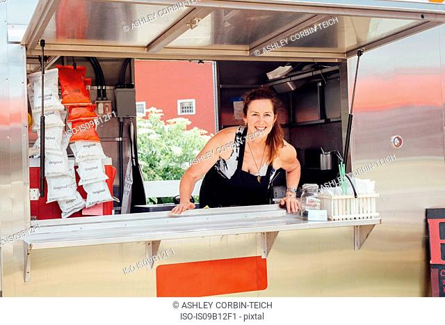Portrait of woman leaning forward at hatch of food stall trailer