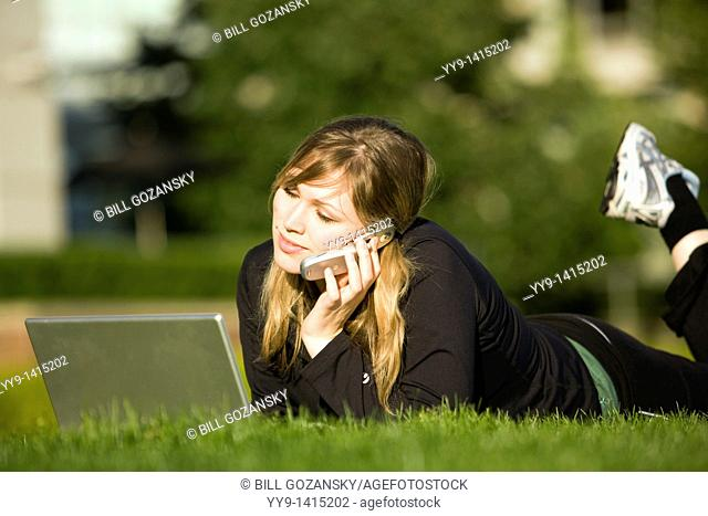 Young woman with laptop computer and cell phone - Vancouver, British Columbia, Canada