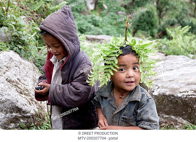 Boy playing with mobile phone and another with leaf of fern, Nepal