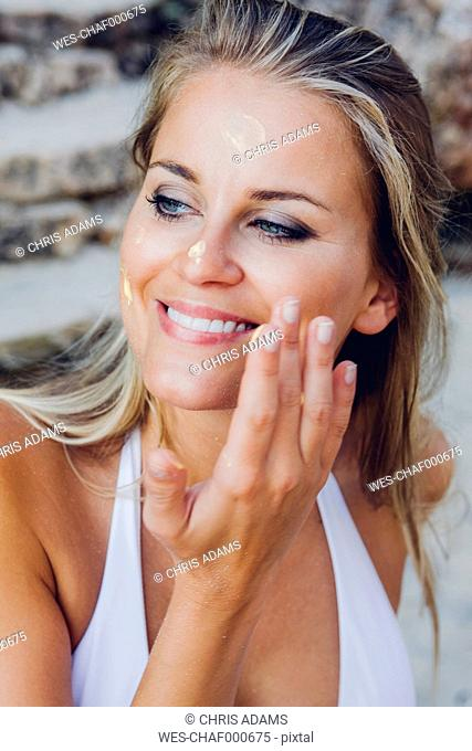 Woman applying sunscreen lotion on her face