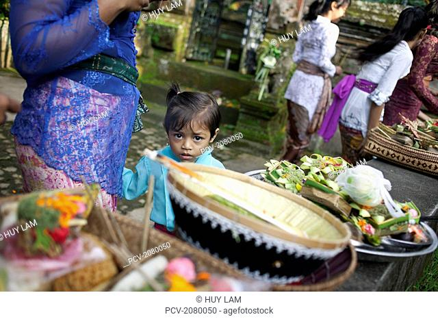 Young girl watching her mother prepare offerings for the Kuningan Festival; Bali, Indonesia