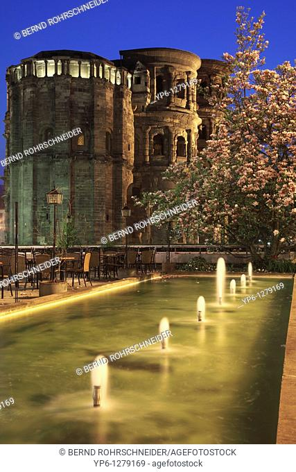 Porta Nigra, illuminated at night, with fountain and blooming magnolia, Trier, Germany