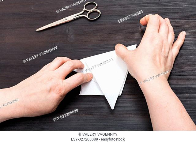 top view of female hands fold sheet of paper to make figure on dark brown wooden table