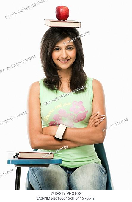 University student balancing a book and apple on her head