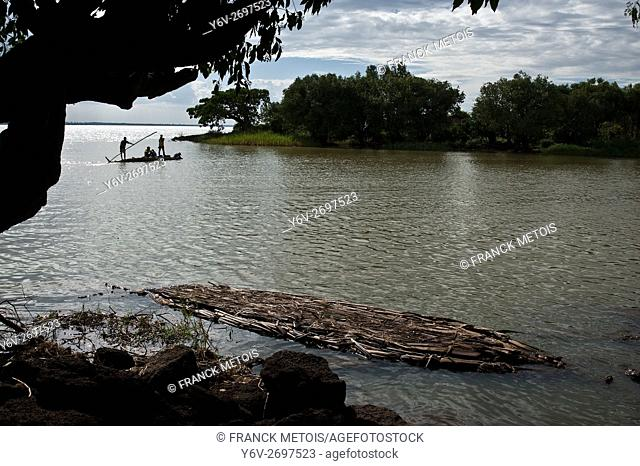 Local people are crossing the Blue Nile river on a papyrus boat. In the background, Lake Tana ( the source of the river)